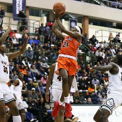 Young's DJ Steward (21) twists in the air to make a shot against Morgan Park.