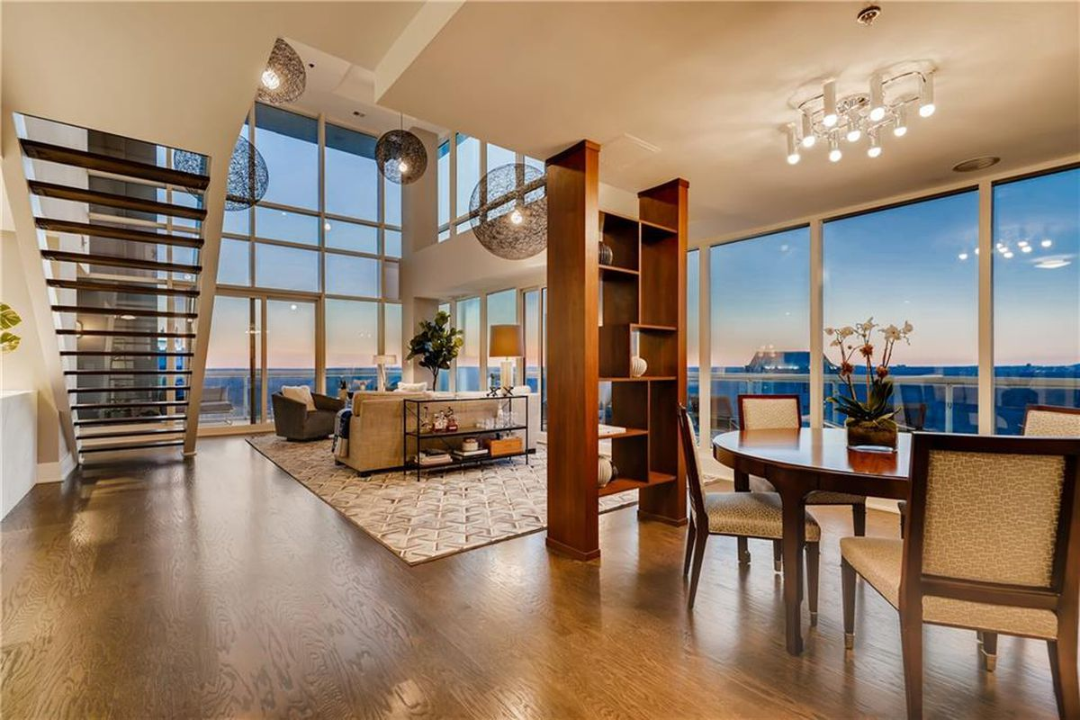 A huge living and dining space with giant windows a skyline beyond.