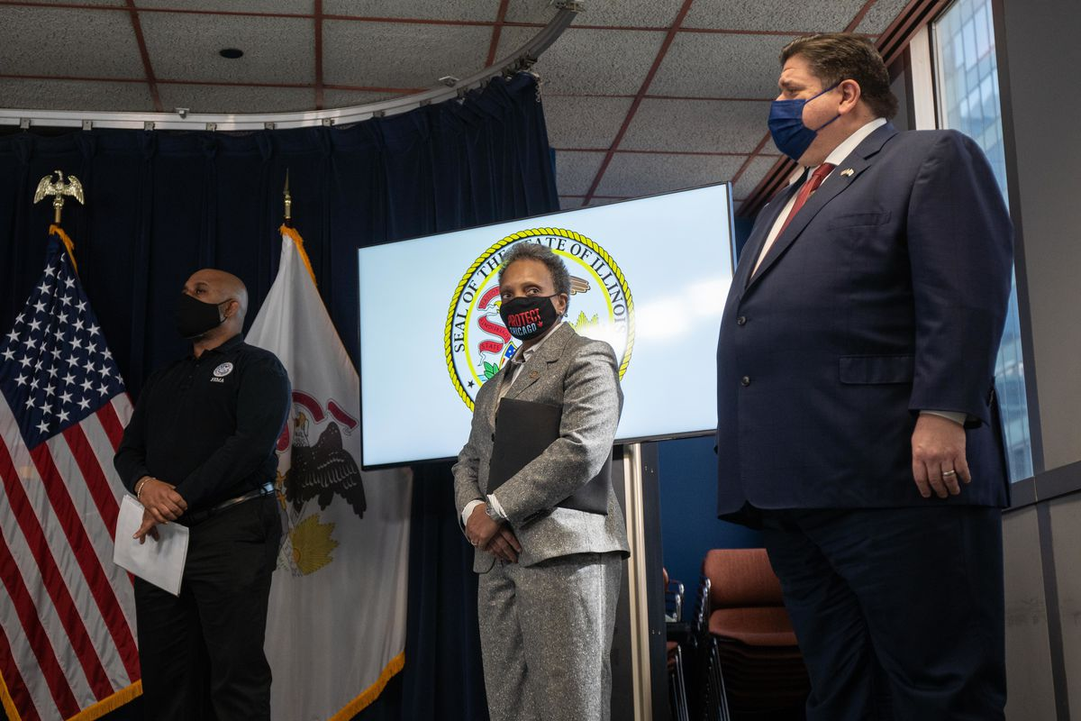 Mayor Lori Lightfoot, center, and Gov. J.B. Pritzker, right, listen during a news conference at the Thompson Center last month.