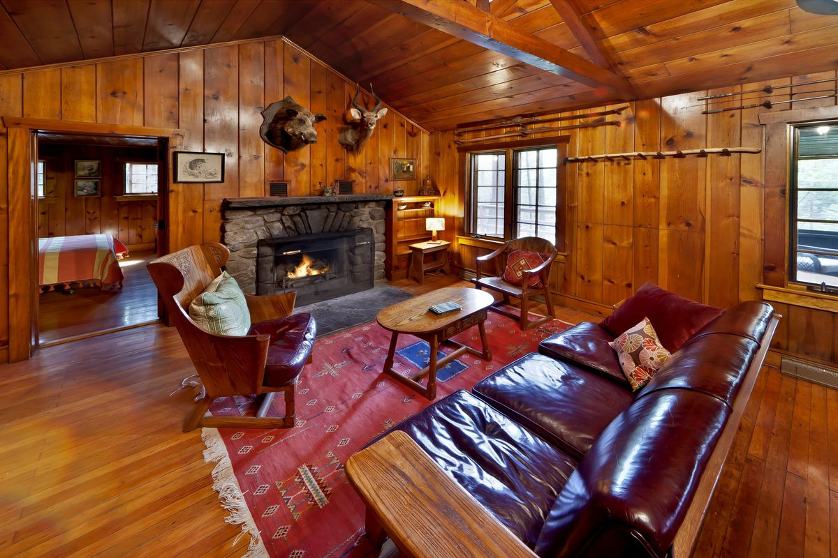 The interior of a cabin in Milford. The walls and floor are wooden. There is a couch, chairs, fireplace, and a patterned area rug. There are preserved animal heads hanging on the wall above the fireplace.