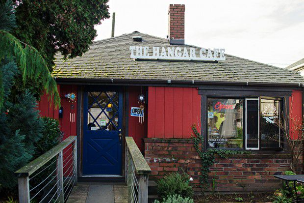 The exterior of The Hangar Cafe, with red painetd wood, a blue door, and a wooden walkway leading up to the entryway