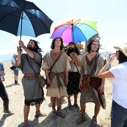 Sam Petersen, who plays Lemuel, Jackson VanDerwerken, who plays Nephi, Mace Sorensen, who plays Laman, and Cooper Sutton, who plays Sam, use umbrellas to avoid the sun and heat between takes while filming the Book of Mormon Visual Library at LDS Motion Picture Studios South Campus near Goshen on Friday, July 7, 2017. On the left is Jacqui Newell, costume designer. Christina Torriente-Robey, director, is on the right.