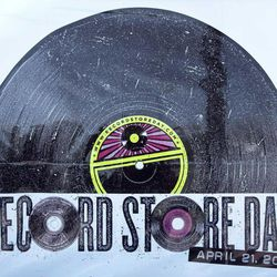 The logo for Record Store Day is seen on a poster, Thursday, April 19, 2012, in Scarborough, Maine. More than 300 new and specially vinyl records will be on sale on Record Store Day, Saturday, April 21.