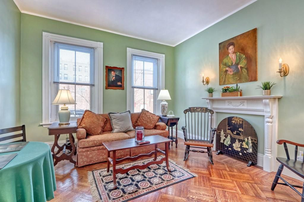 A cozy den with a couch and a coffee table near a fireplace, with a painting of woman above the fireplace.