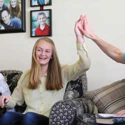 Julia and her dad Dave high-five during a game during family home evening Monday, May 11, 2015, at home in Murray.