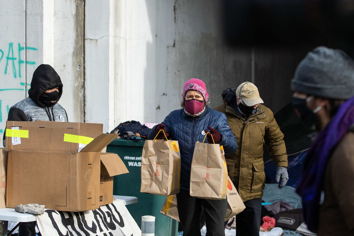 People receive food during a food re-distributing initiative near an encampment of people experiencing homelessness Thursday on West Lawrence Avenue and North Lake Shore Drive in the Uptown neighborhood.