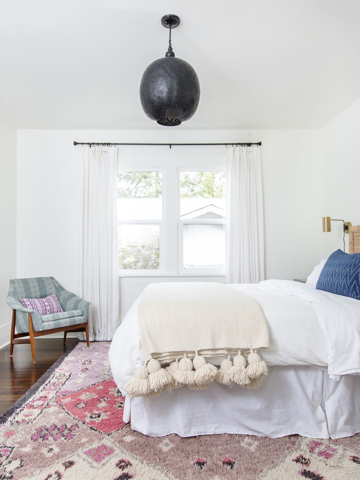 A bedroom. There is a bed with white bed linens and an off-white blanket. There is a patterned area rug under the bed. There is an arm chair and a window with white curtains.