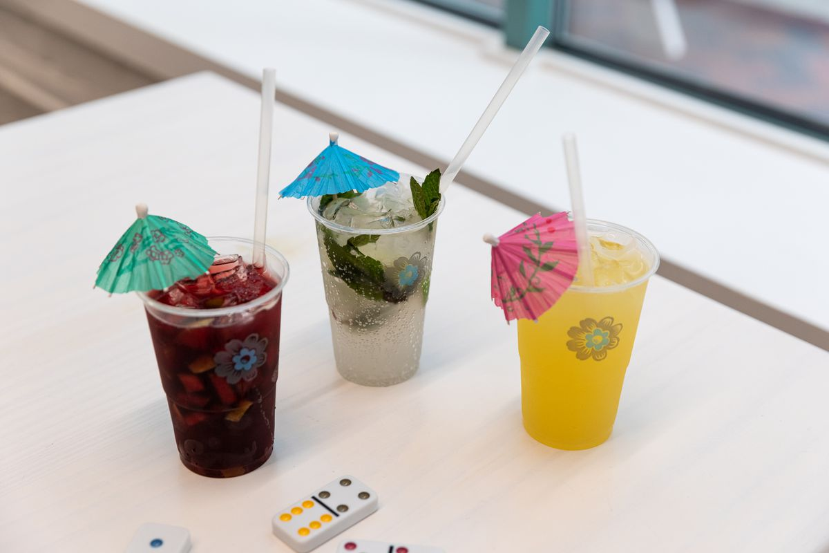 All three drinks are in plastic cups with straws and umbrellas. The sangria is dark red. The mojito is clear with green mint leaves throughout. The lemonade is a dark yellow color.