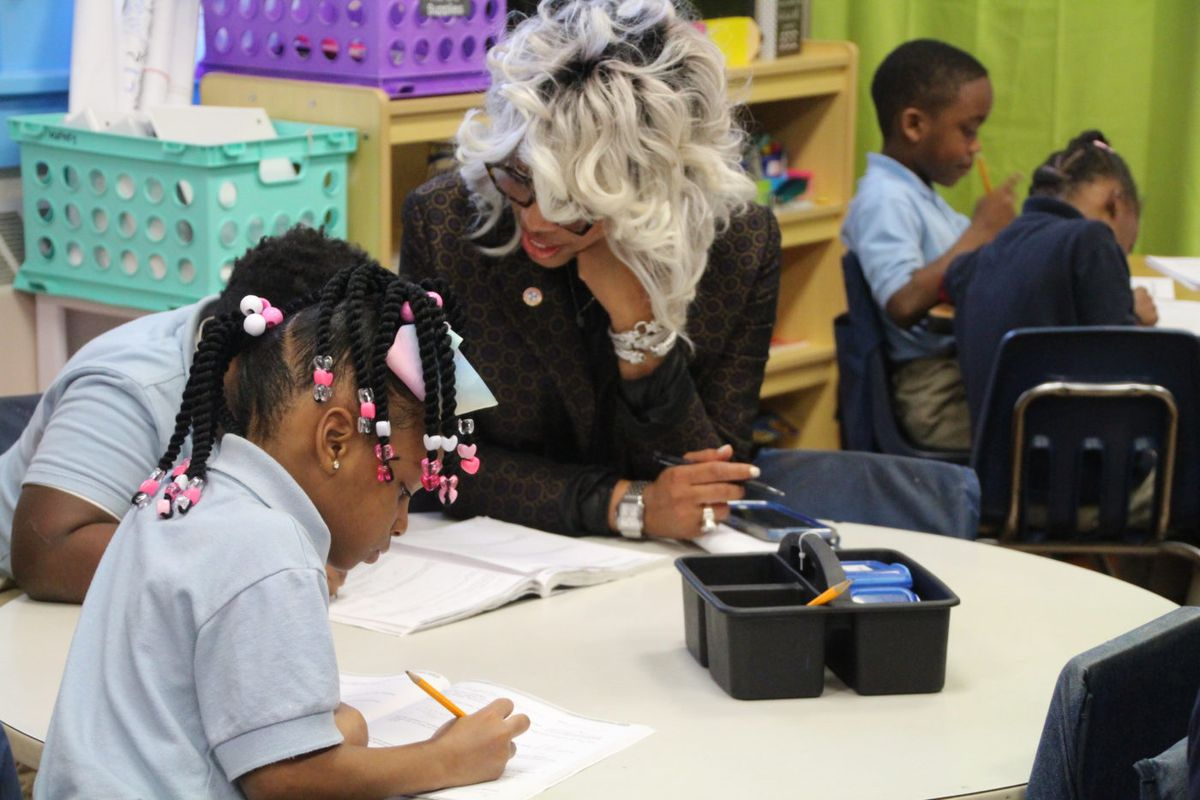 Sharon Griffin helps students with their math lesson during the education commissioner's visit.