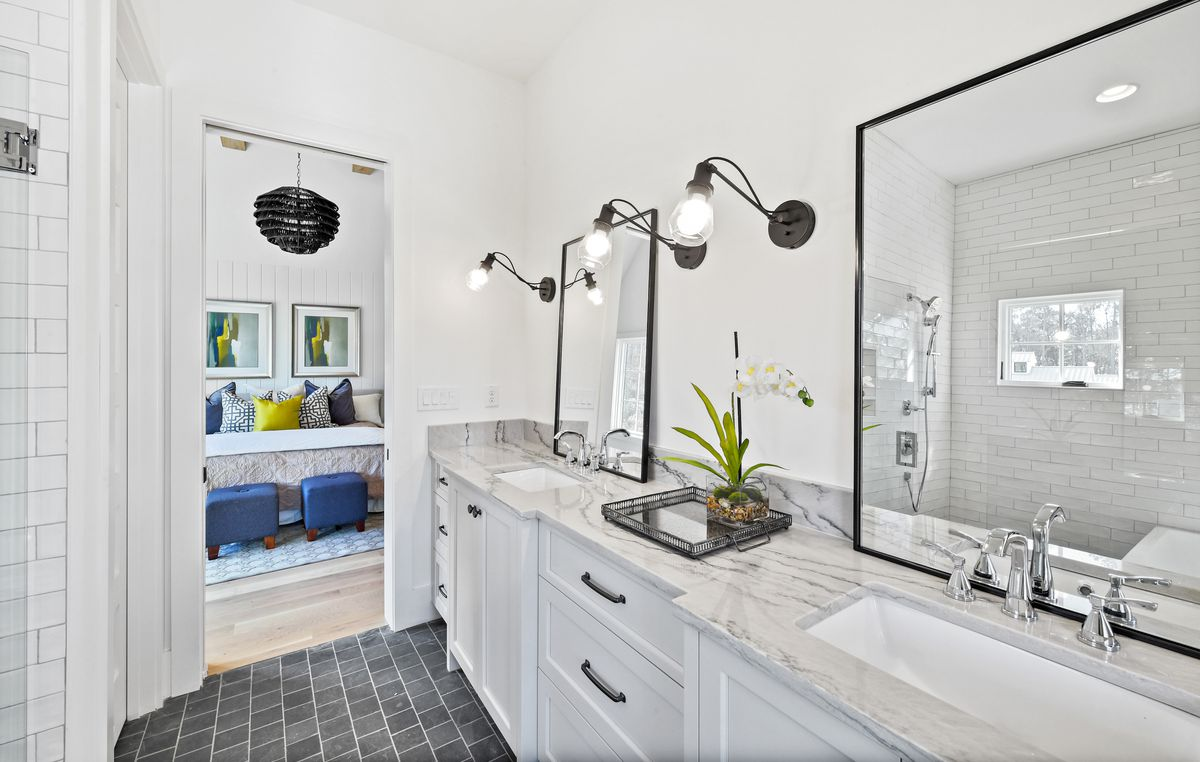 Master bathroom with double vanity, two framed mirrors, and dark tile floor.