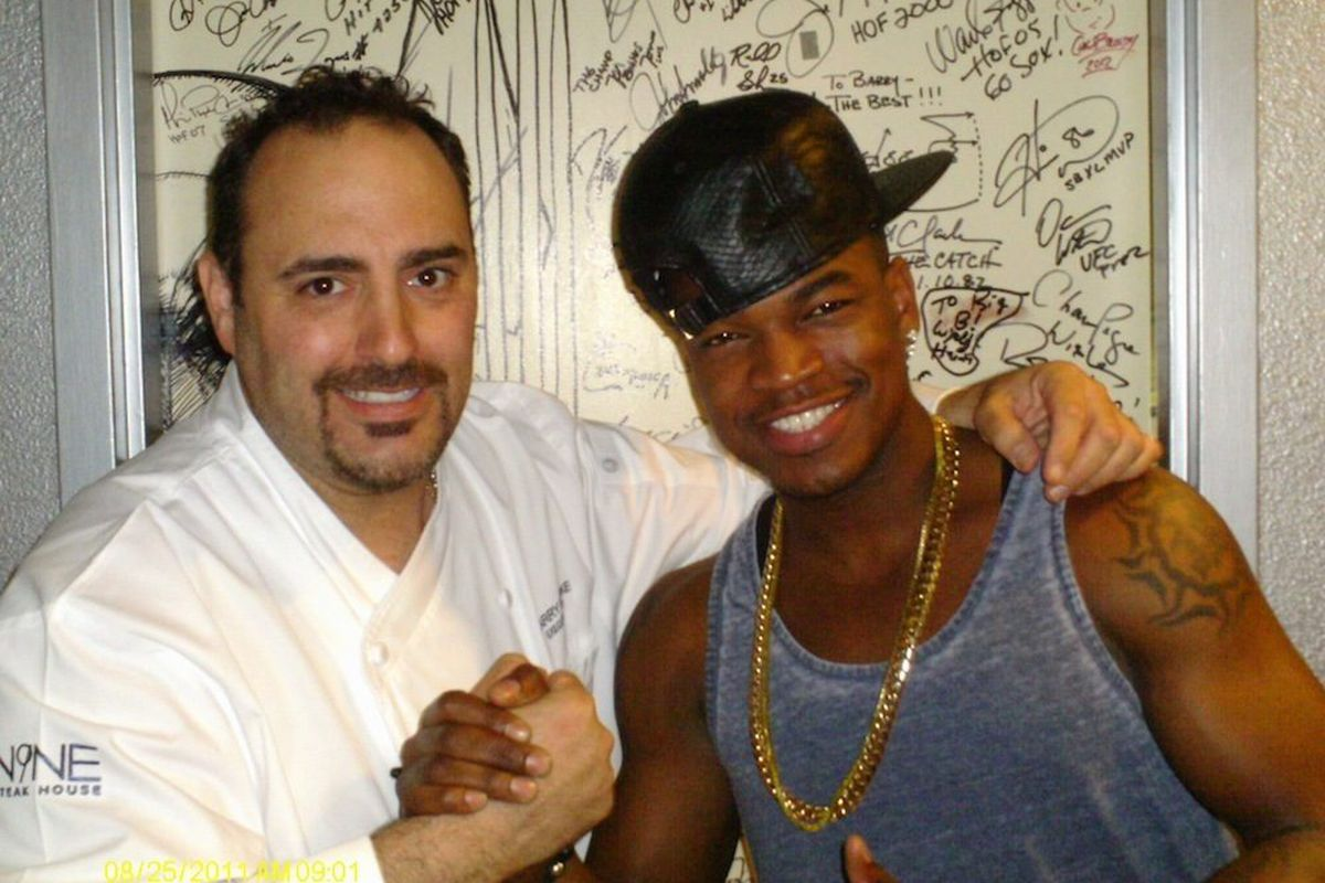 Ne-Yo and executive chef Barry Dakake pose in front of the celebrity Shake Down Door at N9NE Steakhouse.