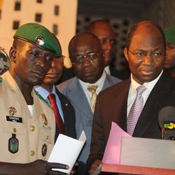 Coup leader Capt. Amadou Haya Sanogo, left, stands with Burkina Faso Foreign Minister Djibrill Bassole, right, as they address the media at junta headquarters in Kati, outside Bamako, Mali Friday, April 6, 2012. Under intense pressure from the nations bordering Mali, Sanogo, the junior officer who seized control of the country in a coup last month signed an accord agreeing to return the country to constitutional rule. The announcement was made late Friday, only hours after separatist rebels in the country's distant north declared their independence.