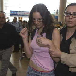 """An Israeli left-wing activists is detained at Ben Gurion Airport near Tel Aviv, Israel, Sunday, April 15, 2012. Four Israeli were arrested for causing a disturbance at the main airport terminal after unfurling a banner bearing the theme of the protest, """"Welcome to Palestine,"""" a police spokesman said. Israel deployed hundreds of police Sunday at its main airport to detain activists flying in to protest the country's occupation of Palestinian areas, defying vigorous Israeli government efforts to block their arrival."""