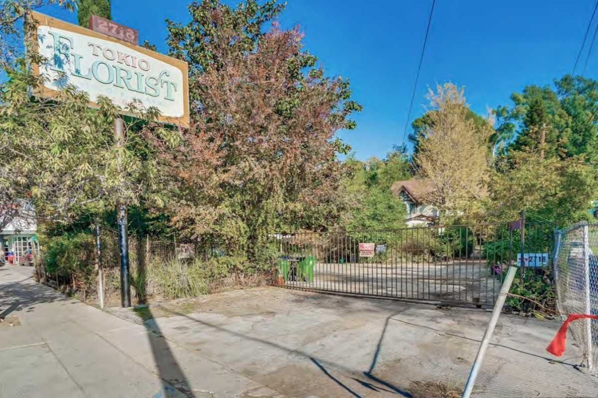 """A pole sign that says """"Tokio Florist"""" in the foreground of an overgrown yard of trees. And fence blocks off the driveway to the parking lot and thee rest of the property."""
