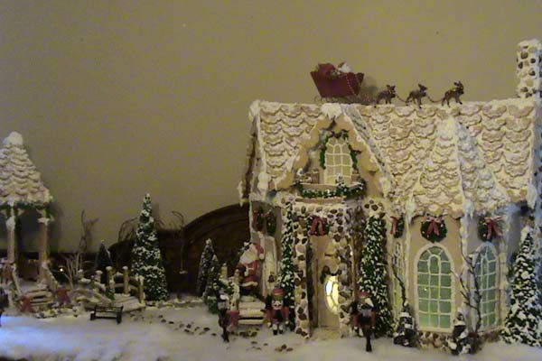 Snowy gingerbread house with sleigh, Santa, and reindeer on the roof.