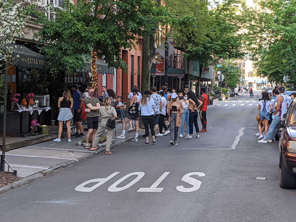 People crowding on the street outside a restaurant in the West Village