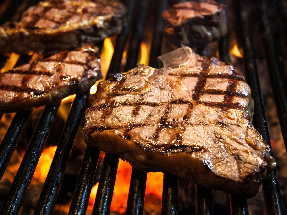 Thick-cut steaks, already singed with grill marks, sit on a grill over an open flame