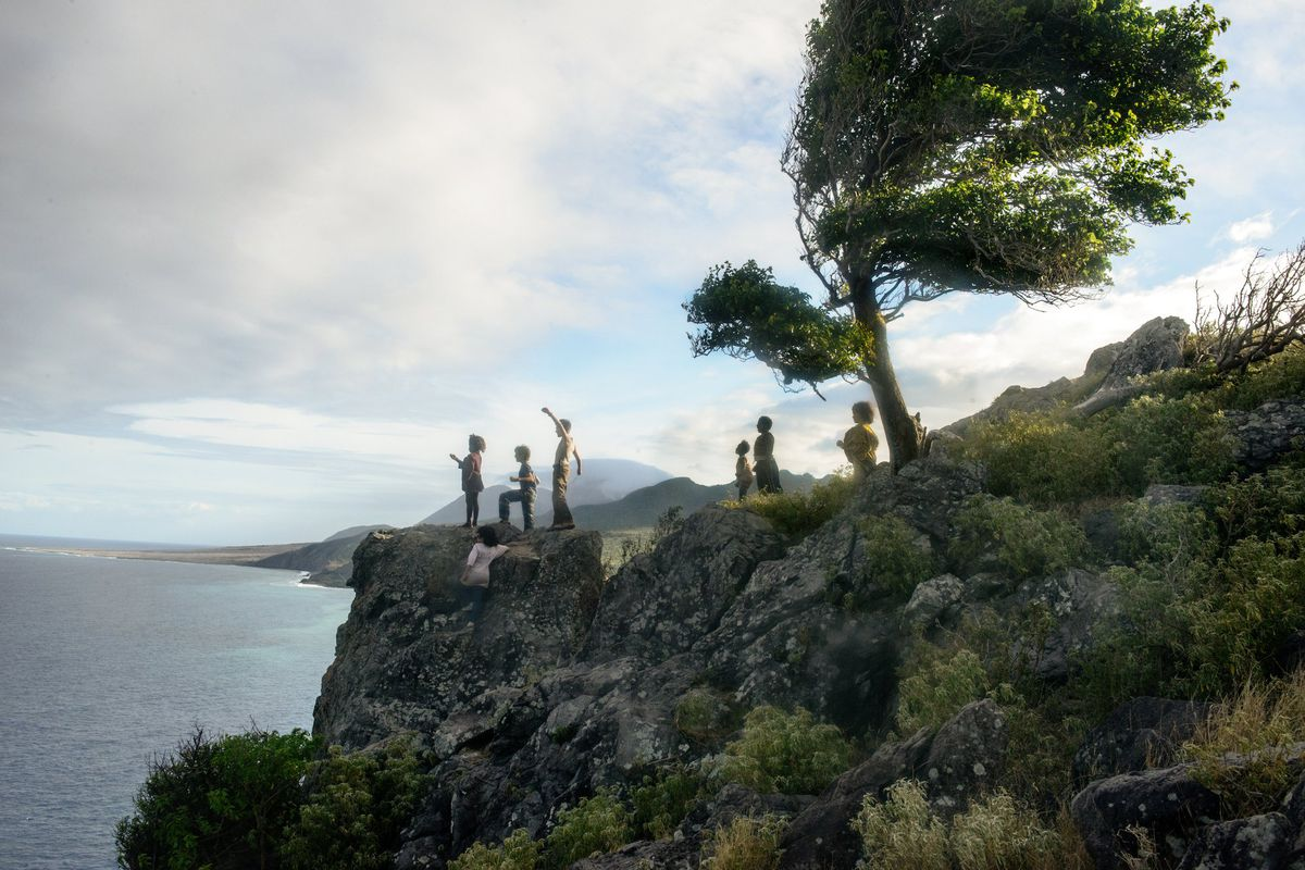 a group of children stand on a rocky cliff overlooking the sea, one with his fist raised triumphantly, in Wendy