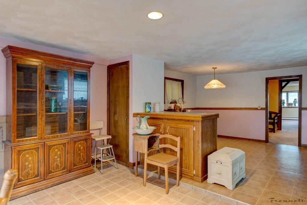 A kitchen and a living room, both largely empty and separated by a short counter.