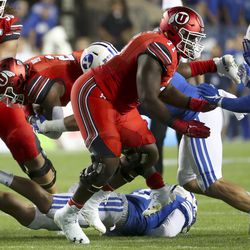 Utah running back Zach Moss (2) is thrown into the air by BYU's defense during the Utah-BYU football game at LaVell Edwards Stadium in Provo on Thursday, August 29, 2019.