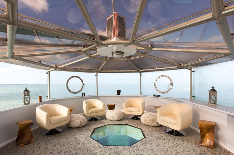 Interior lounge area with views of sea. There are four white arm chairs and windows in a lighthouse style room.