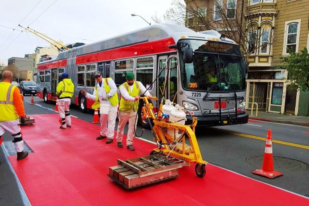 Workers painting bus lanes red in San Francisco.