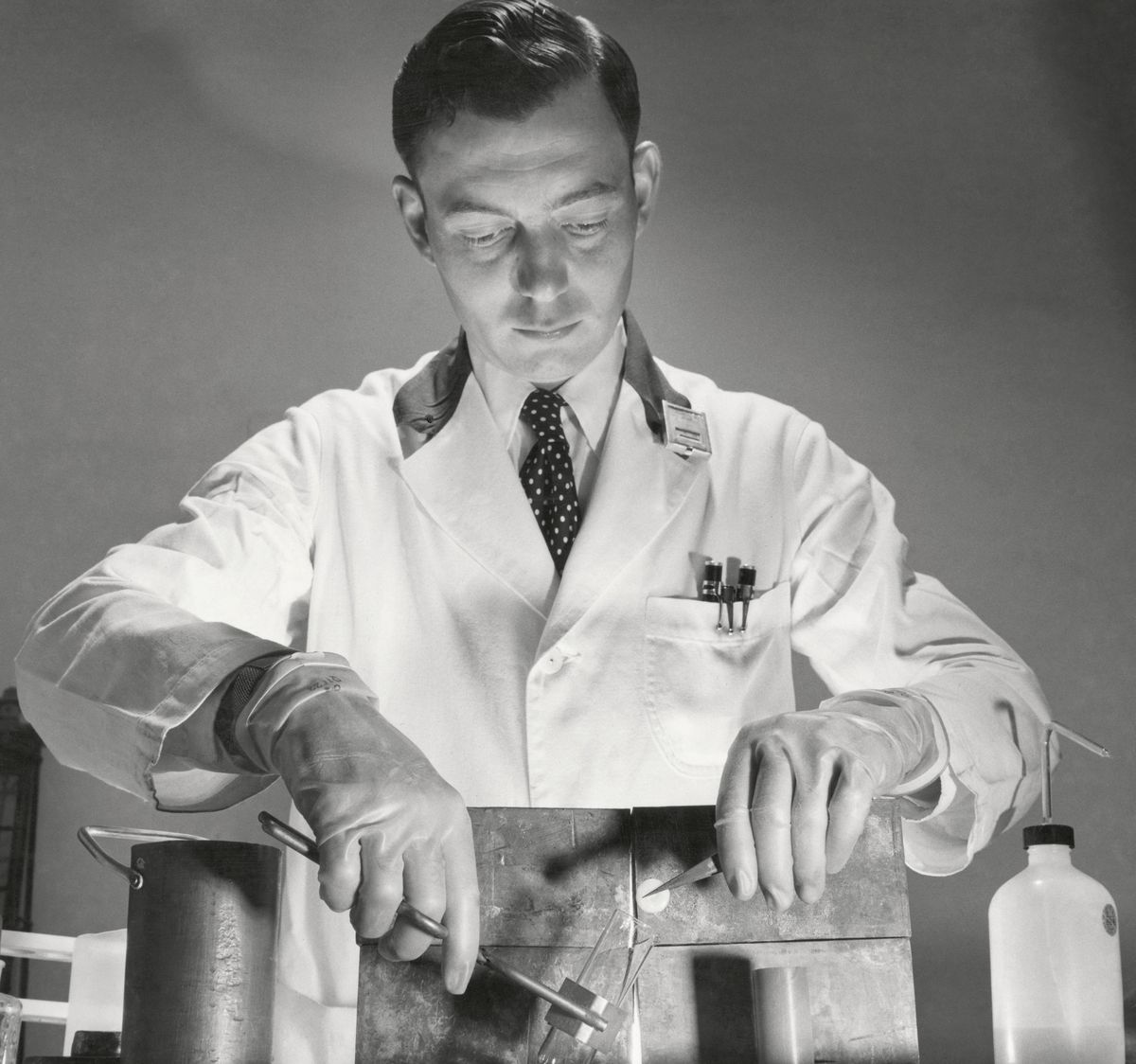 A man in a lab coat uses tongs to take a substance out of a test tube held behind a shield.