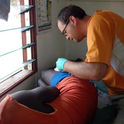 An LDS missionary treats a villager in Vanuatu after Cyclone Pam.