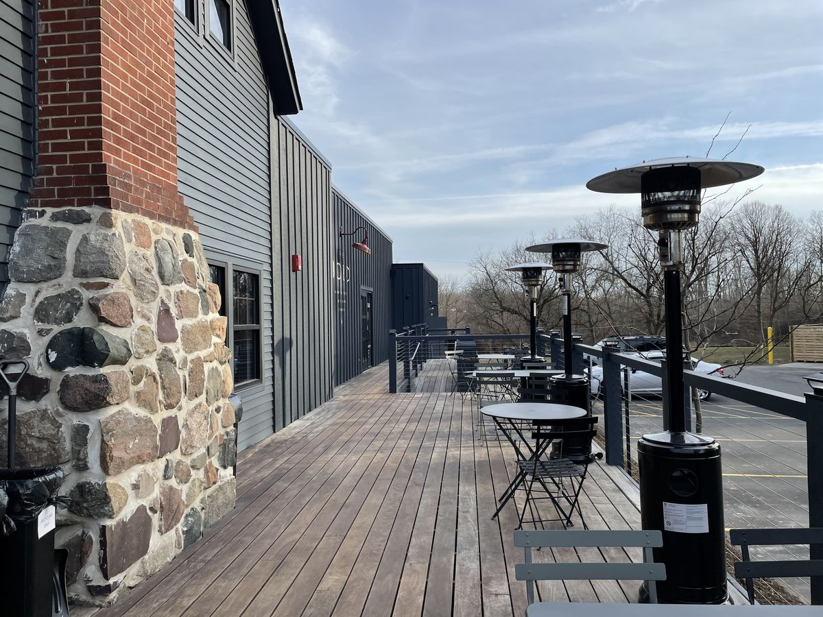 A long patio with a stone and brick chimney and three space heaters lines the edge of the parking lot at Dixboro Project in Ann Arbor