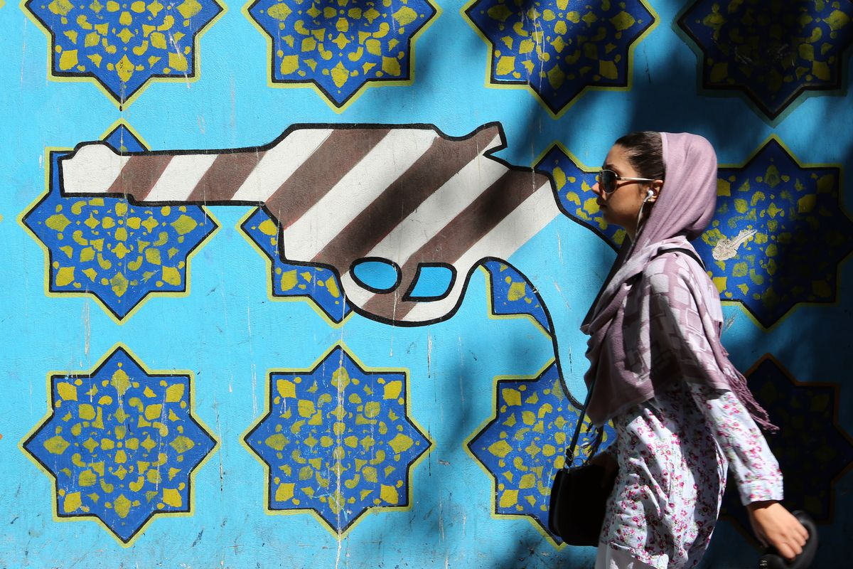 An Iranian woman walks past a mural at the former US Embassy building in Tehran.