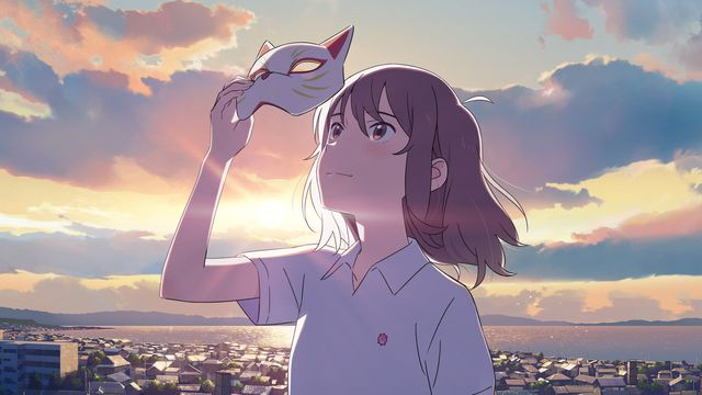 a girl holds up a cat mask