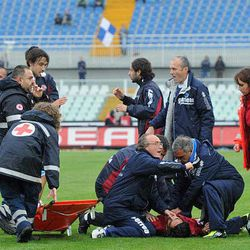 Medics assists Livorno's Piermario Morosini laying on the turf of the Pescara's Adriatico stadium, central Italy, Saturday, April 14, 2012, after he collapsed during a Serie B soccer match between Pescara and Livorno. Morosini, who was on loan from Udinese, fell to the ground in the 31st minute of the match and received urgent medical attention on the pitch. A defibrillator was also used on the 25-year-old. The match was called off, with the other players leaving the field in tears.