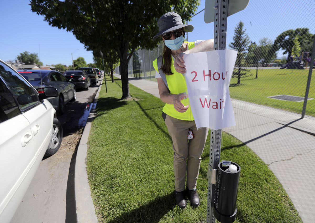Jennifer Thomas, Community Health Centers operations director, hangs a sign letting people in line know they are at the two-hour wait mark as vehicles wrap around the block waiting for COVID-19 testing outside of Glendale Middle School in Salt Lake City on Monday, June 22, 2020.