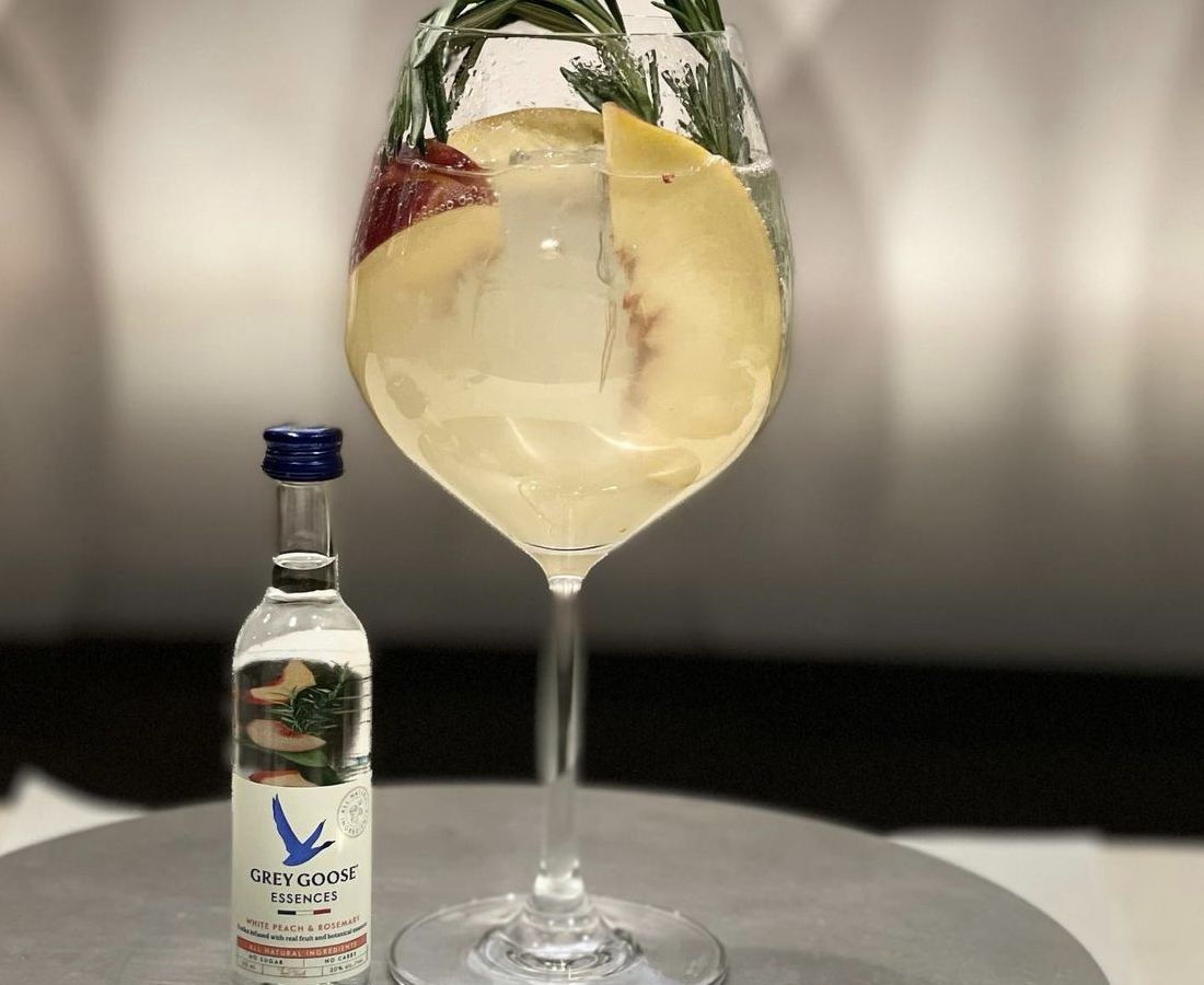 The clear spritz is in a very large wine glass, filled with ice cubes and peaches, as well as a sprig of rosemary.