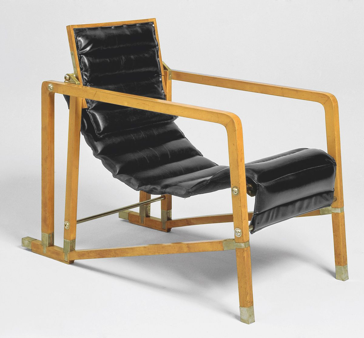A chair made with wooden frame and curved leather seat.