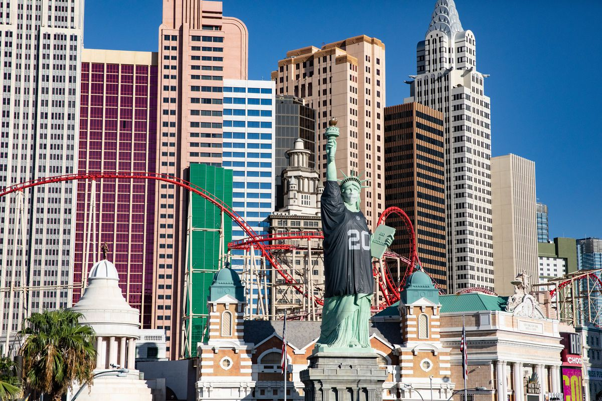 A replica of the Statue of Liberty wears a Las Vegas Raiders jersey in front of a resort that duplicates the New York City skyline