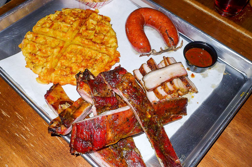 A tray of barbecue including ring sausage, ribs piled helter skelter, and a giant waffle.