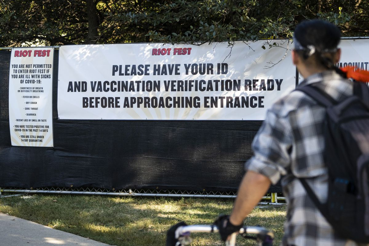 Festival-goers walk past signs at the entrance to Riot Fest on Day 1 in Douglass Park, Thursday afternoon, Sept. 16, 2021.