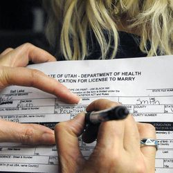 Diana Smith fills out a marriage license on the back of Karen Brinkerhoff outside the Salt Lake County clerk's office after a federal judge ruled that Amendment 3, Utah's same-sex marriage ban, is unconstitutional on Friday, Dec. 20, 2013.