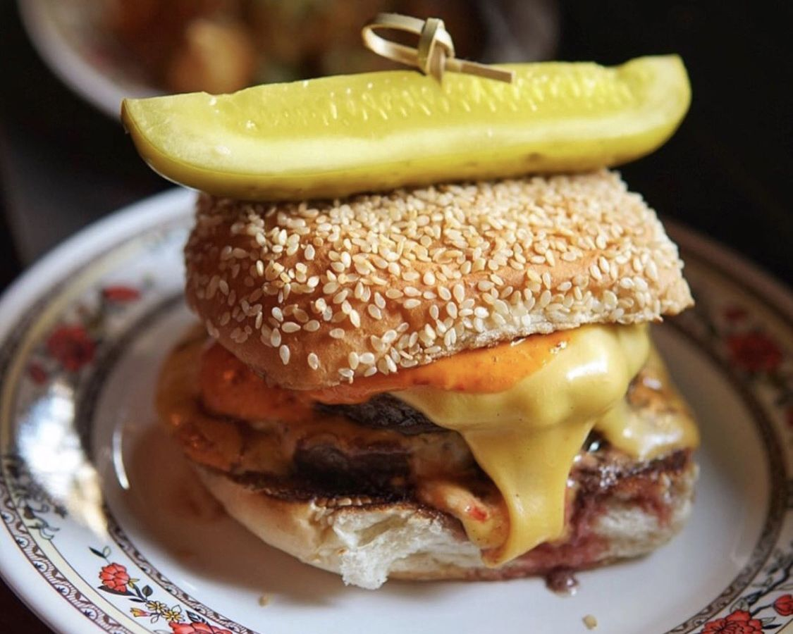 A cheese burger placed on a white plate with a pattern along the border. The cheese burger is sandwiched in a sesame bun with a giant sliced pickle on top held together by a toothpick