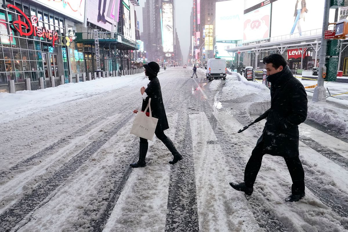 People cross the street in Times Square on December 17, 2020 in New York, the morning after a powerful winter storm hit the US northeastern states.