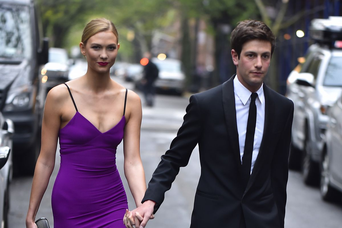 The couple, dressed up for a formal event, crosses the street.