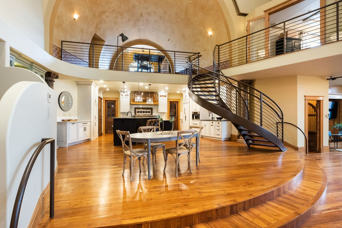 An open-concept dining room and kitchen features a balcony up above with a swirling staircase leading up to it.