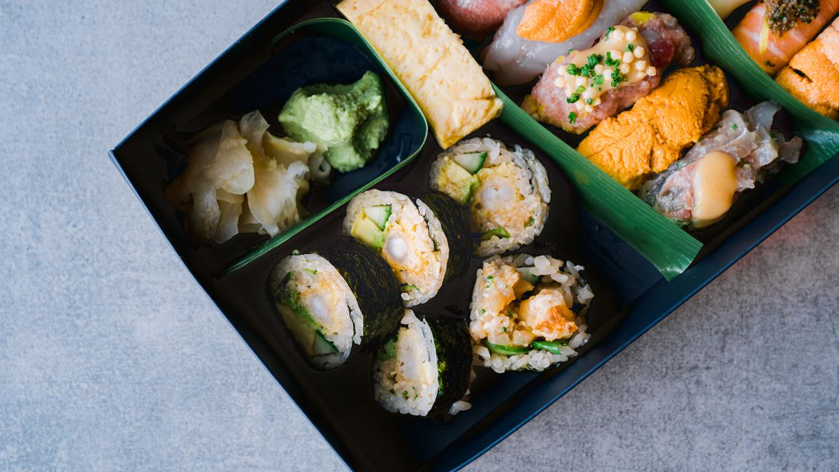 A close-up picture of sushi, ginger, and wasabi arranged in a blue to-go box