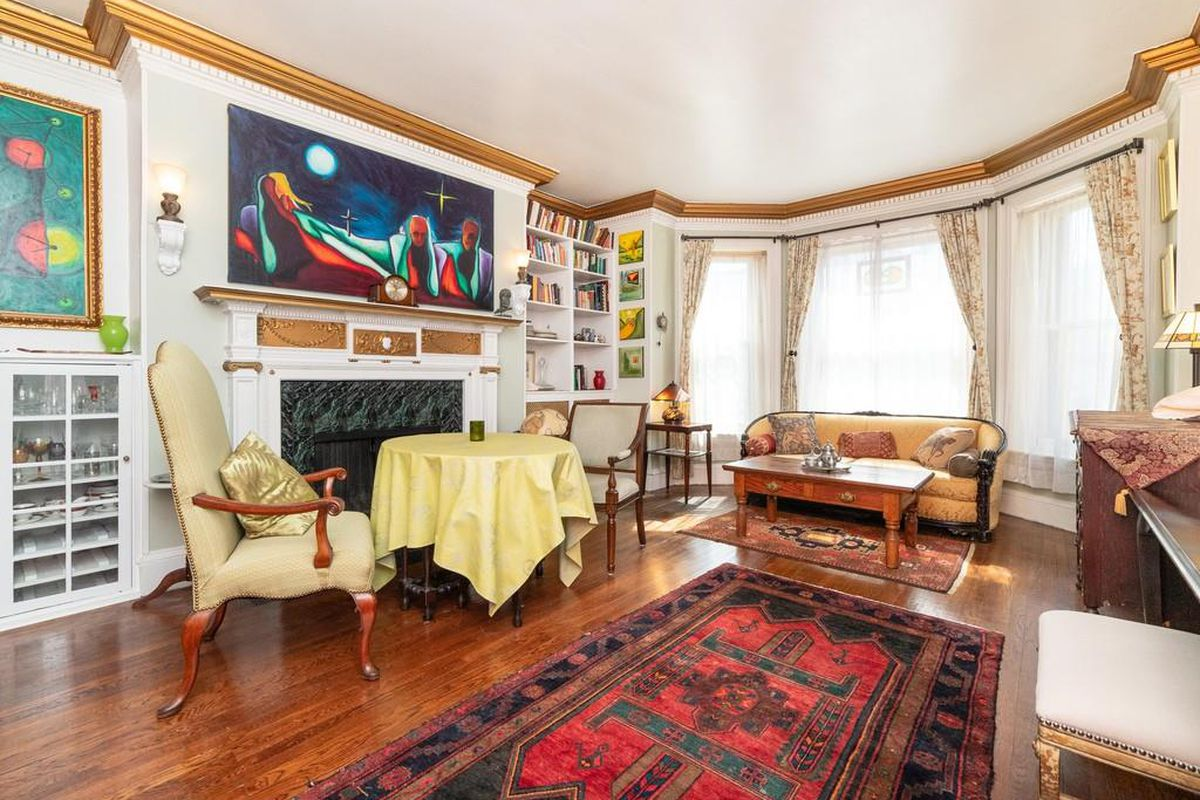 A spacious oval living room with a bay window and a fireplace, and there's furniture.