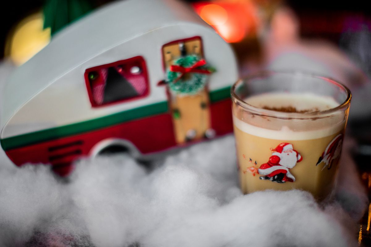A cocktail in a brown glass with santas on it sits in a bed of white cotton fluff next to a Christmas-themed model of a trailer.