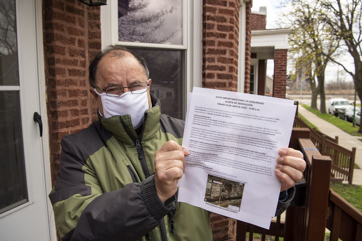Little Village resident Ballar Sanchez lives only a few blocks away from the Crawford power plant, where the smokestack was demolished. He's holding the notice distributed to residents about the implosion.