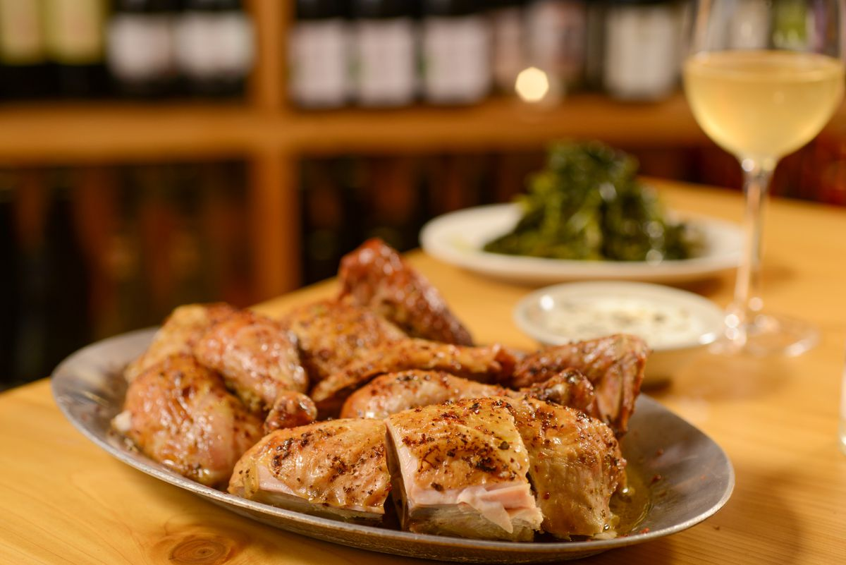 A plate of roast chicken sits on a light wood table next to a glass of white wine.