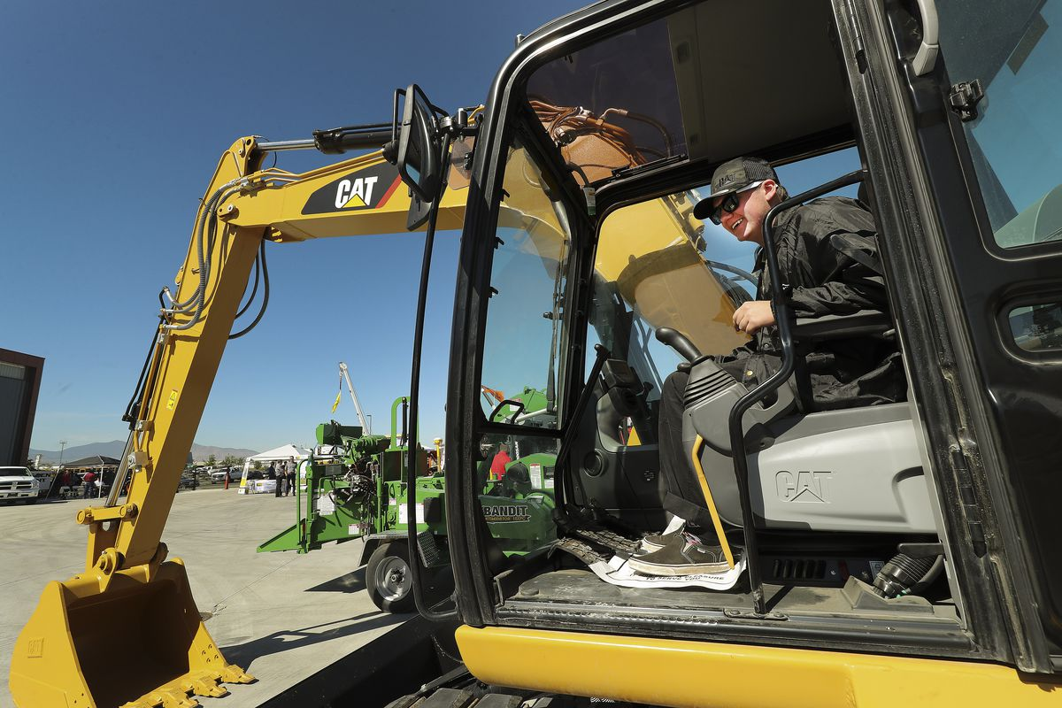 Caden Bringhurst climbs into a front loader as high school students look over Salt Lake Community College'sWestpointe Workforce Training & Education Center in Salt Lake City on Friday, Sept. 13, 2019.