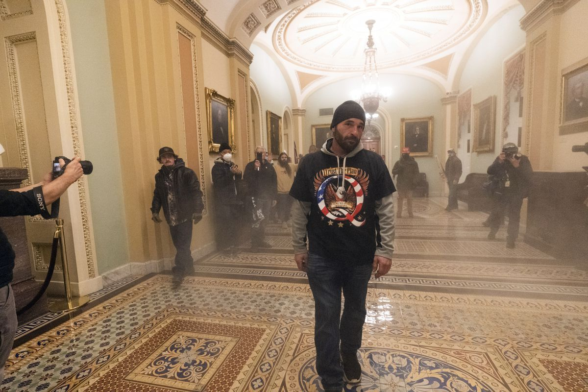 Smoke fills the walkway outside the Senate Chamber as supporters of President Donald Trump are confronted by U.S. Capitol Police officers inside the Capitol Wednesday.